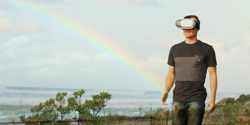 man wears VR goggles missing the rainbow and ocean view.
